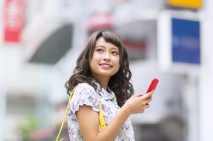 街中でスマートフォンを持ち微笑む女性の素材 [FYI00465782]