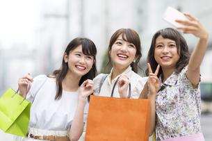 街中で写真を撮る女性3人の素材 [FYI00465784]
