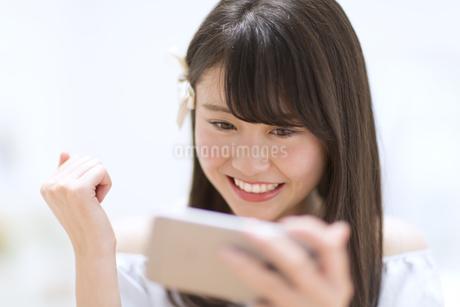 スマートフォンを見てガッツポーズをする女性の素材 [FYI00465901]