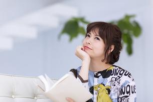 ソファーに座って本を持ち考え込む女性の素材 [FYI00467208]