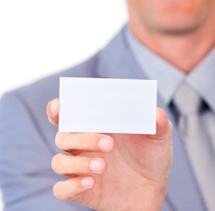 Charming businessman holding a white cardの素材 [FYI00482204]