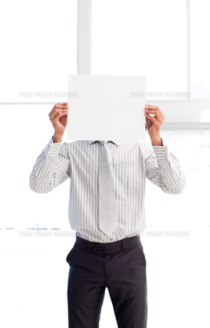 Businessman presenting a white card in front of his faceの素材 [FYI00482870]