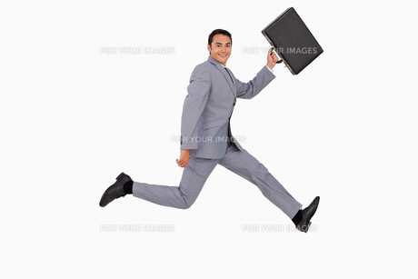 Portrait of a businessman running with a suitcaseの素材 [FYI00484991]