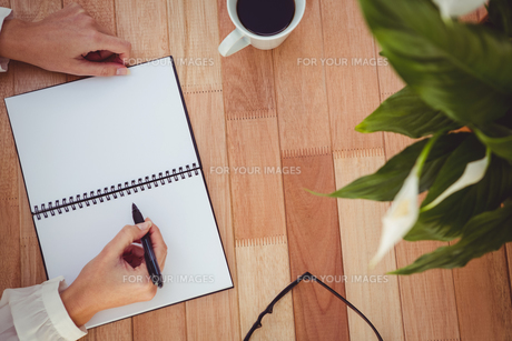 Cropped image of woman writing on notepadの素材 [FYI00486245]