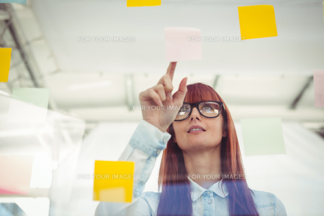 Attractive hipster woman pointing sticky notesの素材 [FYI00486251]
