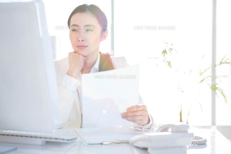 Smiling businesswoman using computerの素材 [FYI00486436]