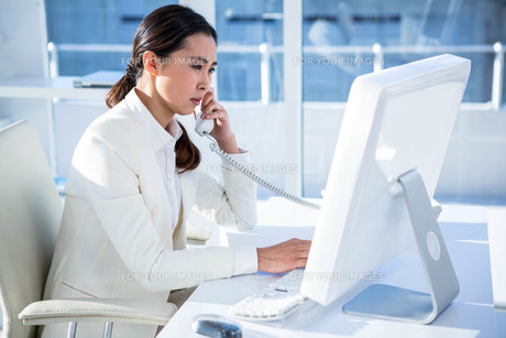 Smiling businesswoman using computer and telephoneの素材 [FYI00486438]
