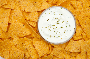 Bowl of dip with herbs surrounded by nachosの素材 [FYI00487229]