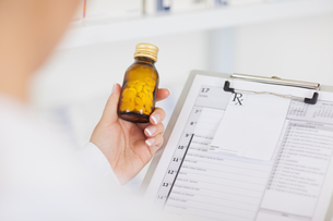 Pharmacist holding a drug bottle and a clipboardの素材 [FYI00487292]