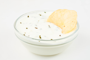 Bowl of white dip with herbs and a nacho dipped in itの素材 [FYI00487452]