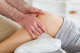 Man massaging a womans kneeの素材 [FYI00487558]