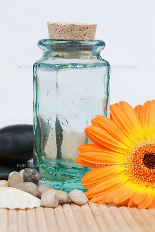 A glass flask with round smooth pebbles and a sunflowerの素材 [FYI00487813]