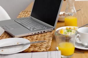 Laptop on a kitchen table. Working having breakfastの素材 [FYI00488284]