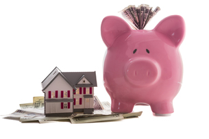 Close up of a pink piggy bank with dollars beside miniature house modelの素材 [FYI00488391]