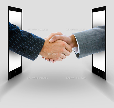 Businessmen shaking hands from digital tabletsの素材 [FYI00488657]
