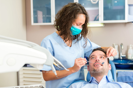 Young attractive man being cured by a dentistの素材 [FYI00659669]