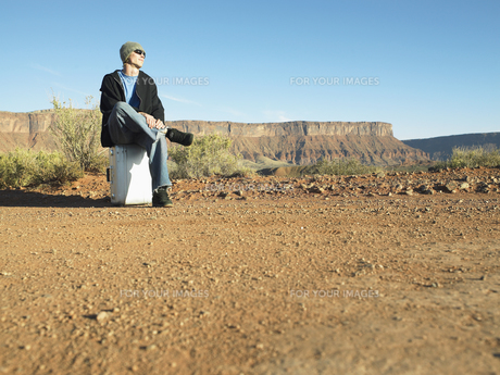 Young man hitchhiking in desertの素材 [FYI00901122]