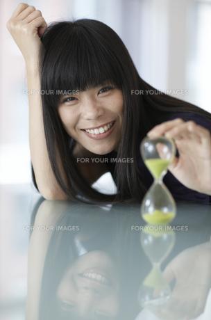 Mid-Adult Woman Holding Hourglassの素材 [FYI00907029]