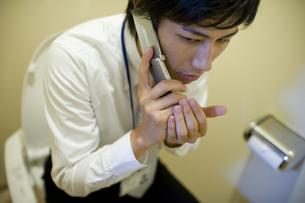 トイレでこっそり電話している男性の素材 [FYI00913629]