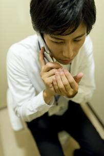 トイレでこっそり電話している男性の素材 [FYI00913681]