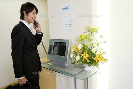 会社の受付で受話器を持った男性の素材 [FYI00913718]