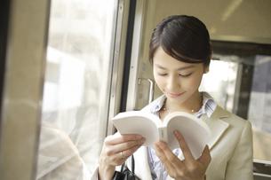 電車内で本を読んでいる女性の素材 [FYI00916543]