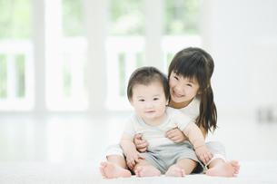 微笑む赤ちゃんを抱きかかえて笑う女の子の素材 [FYI00934581]