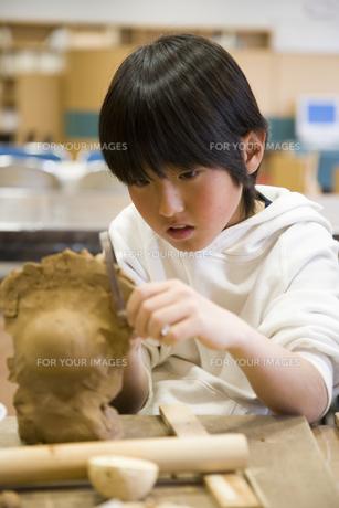 粘土をこねる小学生の男の子の素材 [FYI00945313]
