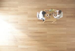 茶色の木の床とデザートを食べる夫婦の素材 [FYI01034013]