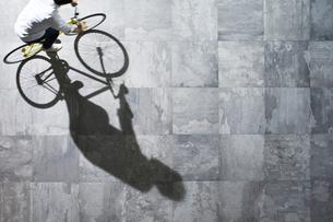 光が差し込む石の床を自転車で走る男性の素材 [FYI01034036]
