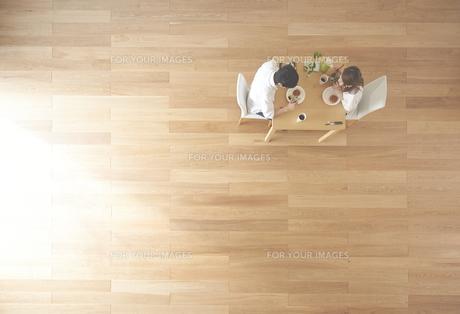 茶色の木の床とデザートを食べる夫婦の素材 [FYI01034141]
