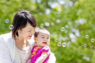 公園でシャボン玉を見て笑う娘と母親の素材 [FYI01075532]