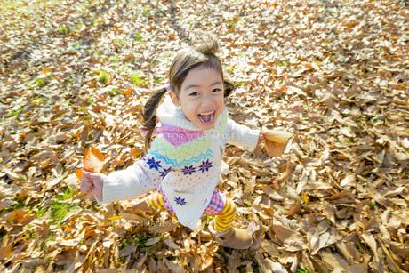落葉の公園を葉っぱを持って走る女の子の素材 [FYI01075605]
