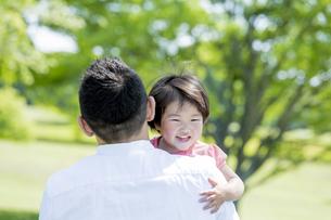 新緑の公園で父親に抱かれる娘の素材 [FYI01075692]