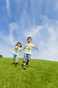 公園を手をつないで走る兄と妹の素材 [FYI01075713]