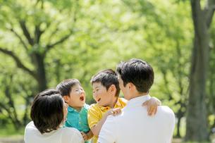 新緑の公園で遊ぶ4人家族の素材 [FYI01075893]