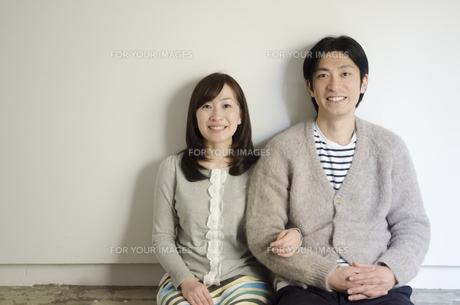 床に座って笑うカップルの素材 [FYI01076877]