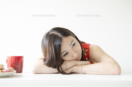 机の上に腕を組み顔を乗せる女性の素材 [FYI01076881]