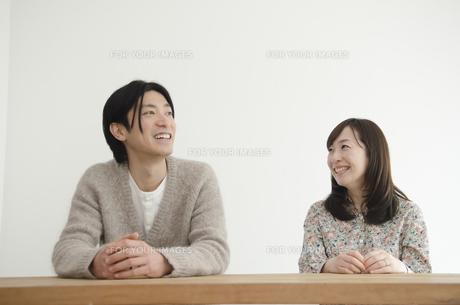 机に手を乗せて笑うカップルの素材 [FYI01076926]