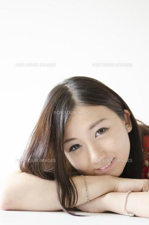 机の上に腕を組み顔を乗せて笑う女性の素材 [FYI01076929]