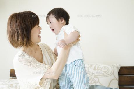 ベッドの上で笑うお母さんと男の子の素材 [FYI01077067]