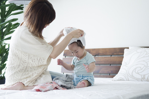 ベッドの上で着替えをする男の子とお母さんの素材 [FYI01077090]