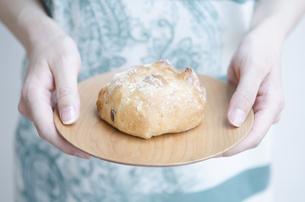 お皿に乗ったパンを持つ女性の手元の素材 [FYI01077092]