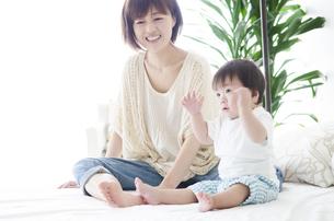 ベッドの上に座るお母さんと男の子の素材 [FYI01077117]