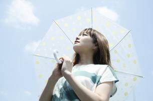 青空をバックに傘を差した女性の素材 [FYI01077123]