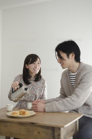 男性のカップにお茶をつぐ女性の素材 [FYI01077132]