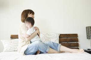 ベッドの上で抱き合うお母さんと男の子の素材 [FYI01077139]