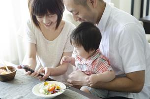 スマートフォンを見て笑っている家族の素材 [FYI01077227]