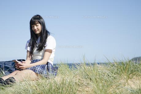 ビーチに座って携帯電話をいじっている制服姿の女の子の素材 [FYI01077232]