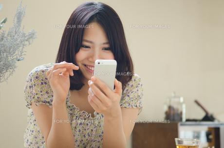 部屋の中でスマートフォンを操作する女性の素材 [FYI01077399]